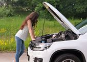 Girl Examining Her Broken Car On The Country Road. Young Brunette Woman Trying To Repair Her Broken  poster
