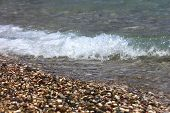 Bright Colorful Stones On The Beach With Clear Clear Water, Foamy Wave. Focus Runs Through The Middl poster