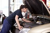 foto of car repair shop  - An attractive woman mechanic working on a car in a repair shop - JPG
