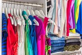 Fashion clothes in walk-in clothing closet or store display for shopping display. Colorful choices o poster
