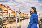 Tourist in Copenhagen. Chinese Asian woman traveler walking in Nyhavn visiting Denmark. City travel, poster