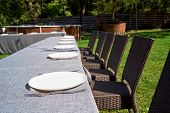 Dinner Table With Empty Ceramic Round Plates And Cutlery On Grey Tablecloth And Chairs In Garden Out poster