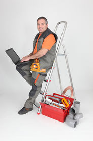picture of washing-machine  - plumber sitting on stepladder with computer - JPG