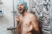 Attractive young cheerful man singing while washing in the shower, wearing shower cap and holding sh poster