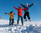 three boy family friends joyfully jump into the sky over snow drifts in the winter, children play poster