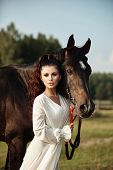 Girl In A Long Dress Stands Near A Horse, A Beautiful Woman Strokes A Horse And Holds The Bridle In poster
