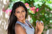 Beautiful Asian Indian girl or young woman photographer happy taking pictures or photographs outside poster