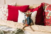 White And Red Pillows On The Bed In The Bedroom, Stuffed Deer Toy Among The Pillows poster