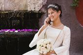 image of quinceanera  - Hispanic girl on cell phone in Quinceanera dress - JPG