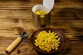 Open Tin Can And Plate With Corn And Can Opener On Wooden Table poster