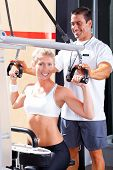 pic of personal trainer  - personal trainer helping client in gym - JPG