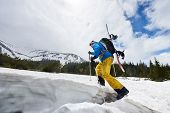 Side View Of Male In Winter Mountain Touring Walking Up With Ski Poles Helping And Carrying Backpack poster