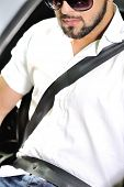 stock photo of seatbelt  - Young man in sunglasses sitting in a car with seatbelt on - JPG