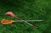 stock photo of lax  - A pair of Girls Lacrosse sticks laying on a turf field forming an X as in LAX - JPG