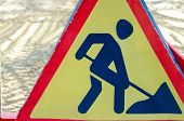 Warning Road Sign Road Repair. Against The Background Of Road Repair With Traces Of Heavy Road Equip poster