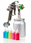 stock photo of air paint gun  - New metal brilliant Spray gun and small bottles with color - JPG