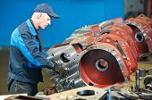 stock photo of assemblage  - adult experienced industrial worker during heavy industry machinery assembling on production line manufacturing workshop - JPG