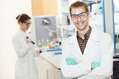 picture of chemistry technician  - Portrait of young smiling male researcher in front of female researcher carrying out scientific test in chemistry laboratory - JPG