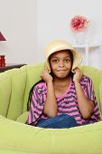 picture of cornrow  - Black child playing while sitting in a green chair - JPG