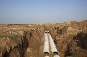 picture of urbanisation  - newly laid pipes in an open trench on a new construction site on the outskirts of Mohali Chandigarh Punjab India - JPG
