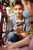 Portrait of cute boy looking at his father while repairing bicycle in garage