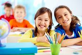 picture of cute kids  - Portrait of two diligent girls looking at camera at workplace with schoolboys on background - JPG