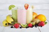 stock photo of fruit shake  - Fruit smoothies with black currant strawberry kiwi orange and banana on white wooden background - JPG