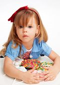 stock photo of greedy  - Greedy girl with pile of sweets laying on the table and with troubled expression on the face - JPG