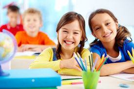 stock photo of schoolboys  - Portrait of two diligent girls looking at camera at workplace with schoolboys on background - JPG