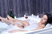foto of recliner  - A beautiful woman in a bath with foam drinking wine - JPG