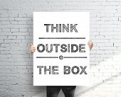 stock photo of thinking outside box  - businessman holding poster with think outside the box - JPG