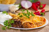 stock photo of enchiladas  - Southwest beef enchilada with sourcream and black beans.