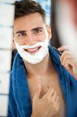 Portrait of smiling handsome shaving man in bathroom