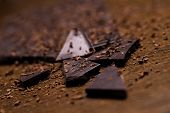 image of grating  - Dark chocolate bar and some powder around it on a wooden surface - JPG