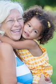 stock photo of granddaughter  - Grandmother hugs her hispanic granddaughter and laughs  - JPG
