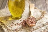 stock photo of flax plant  - Flax seeds in a wooden spoon and linseed oil - JPG