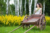Young girl with old wooden cart on the field with green grass and yellow flowers