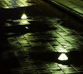 Reflections from streetlights on wet bridge night