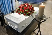 stock photo of crematory  - A coffin with a flower arrangement in a morgue and a burning candle in front - JPG
