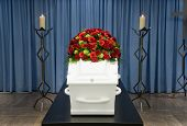 foto of crematory  - A coffin with a flower arrangement in a morgue and a burning candle in front - JPG