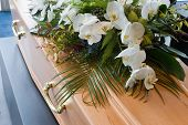 image of mortuary  - A coffin with a flower arrangement in a morgue - JPG