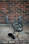 stock photo of unicycle  - A unicycle chained to a bicycle rack - JPG