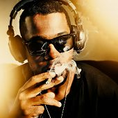 image of joint  - cool african man smoking joint wearing headphones - JPG