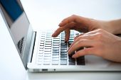 stock photo of peripherals  - Closeup of businesswoman typing on laptop computer - JPG
