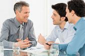 stock photo of conversation  - Group Of Happy Businessmen Having Conversation In Meeting - JPG