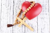 stock photo of rosary  - Heart with rosary beads on wooden background - JPG