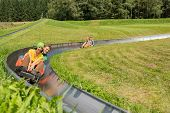 stock photo of luge  - Smiling young couples enjoying summer sledge ride - JPG