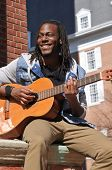 stock photo of reggae  - happy young black man playing the guitar in the city - JPG
