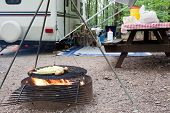 stock photo of trailer park  - Corn and potatoes on an outdoor grill at a public park with a picnic table and camping trailer in the background.