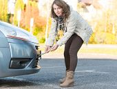 Beautiful woman assembling towing hook to a broken car